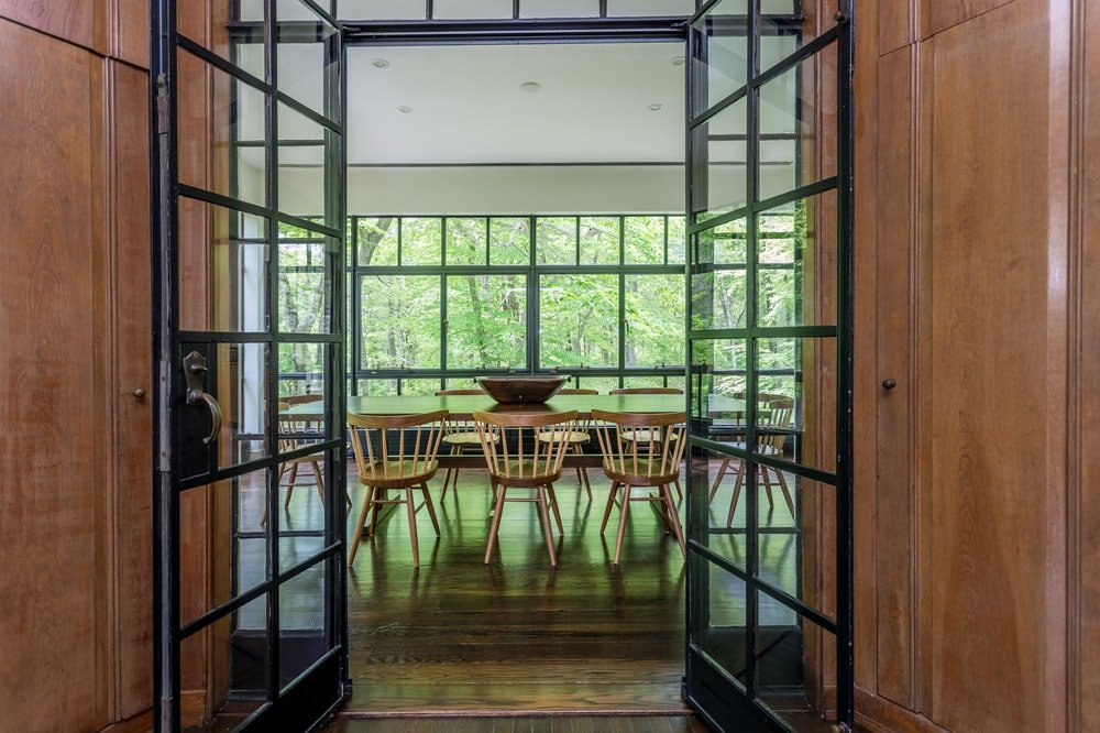 This is a set of glass doors leading to the large dining room bathed in natural lighting from the glass walls. Image courtesy of Toptenrealestatedeals.com.