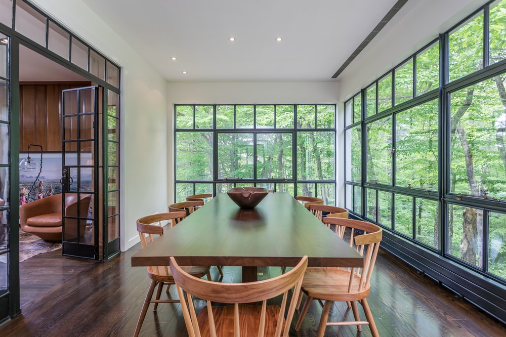 This other view of the large dining table showcases the surrounding large glass walls that also give a view of the surrounding tall trees. Image courtesy of Toptenrealestatedeals.com.
