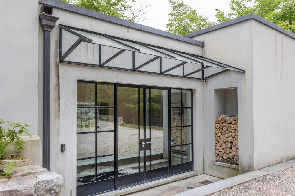 This is a close look at the main entrance of the house that has a set of glass doors topped with a simple awning. Image courtesy of Toptenrealestatedeals.com.