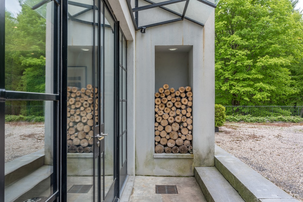 On the side of the glass doors of the entrance is this fire wood storage embedded into the wall that also funsctions to give a rustic feel to the main entrance. Image courtesy of Toptenrealestatedeals.com.