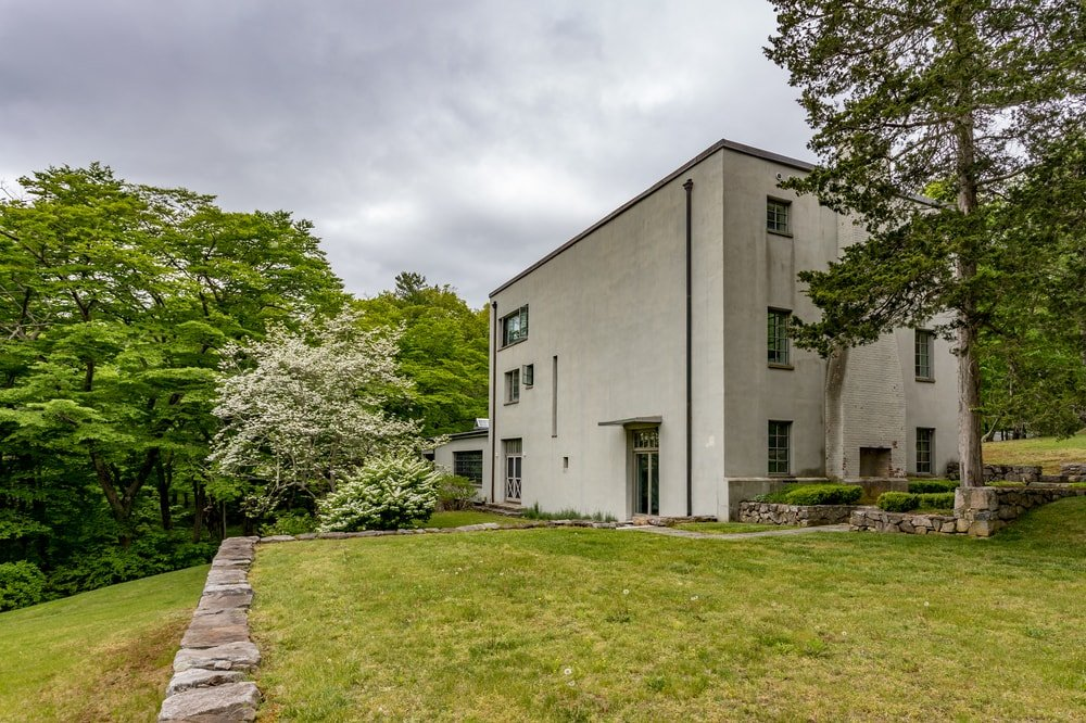 This is the other side of the house showcasing the large exterior wall adorned by the surrounding green landscape of tall trees. Image courtesy of Toptenrealestatedeals.com.