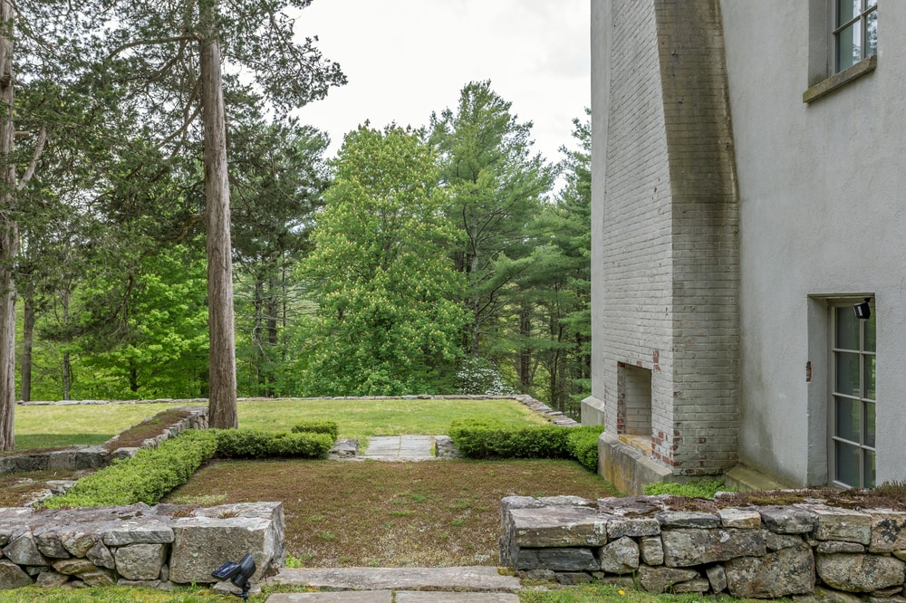 This side of the house has an outdoor fireplace to warm up an open area surrounded by low shrubs. Image courtesy of Toptenrealestatedeals.com.
