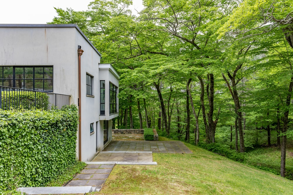 The sire of the house is bordered with tall trees and shrubs on the side. Image courtesy of Toptenrealestatedeals.com.