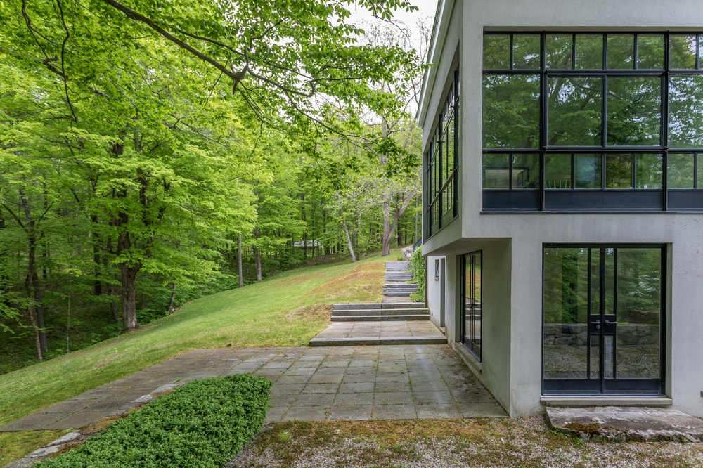 This side of the house shows concrete walkways and steps that run along the white exterior walls filled with glass windows and doors. Image courtesy of Toptenrealestatedeals.com.