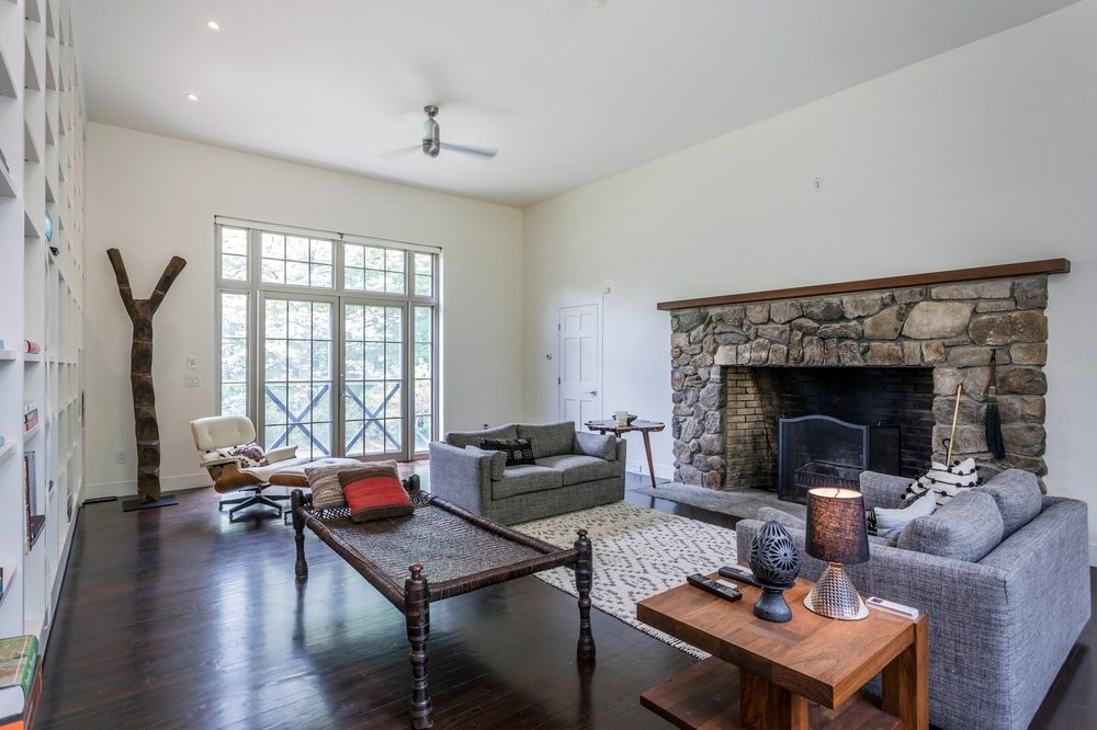 This large fireplace is flanked by gray two-seater armchairs on dark hardwood flooring. Image courtesy of Toptenrealestatedeals.com.