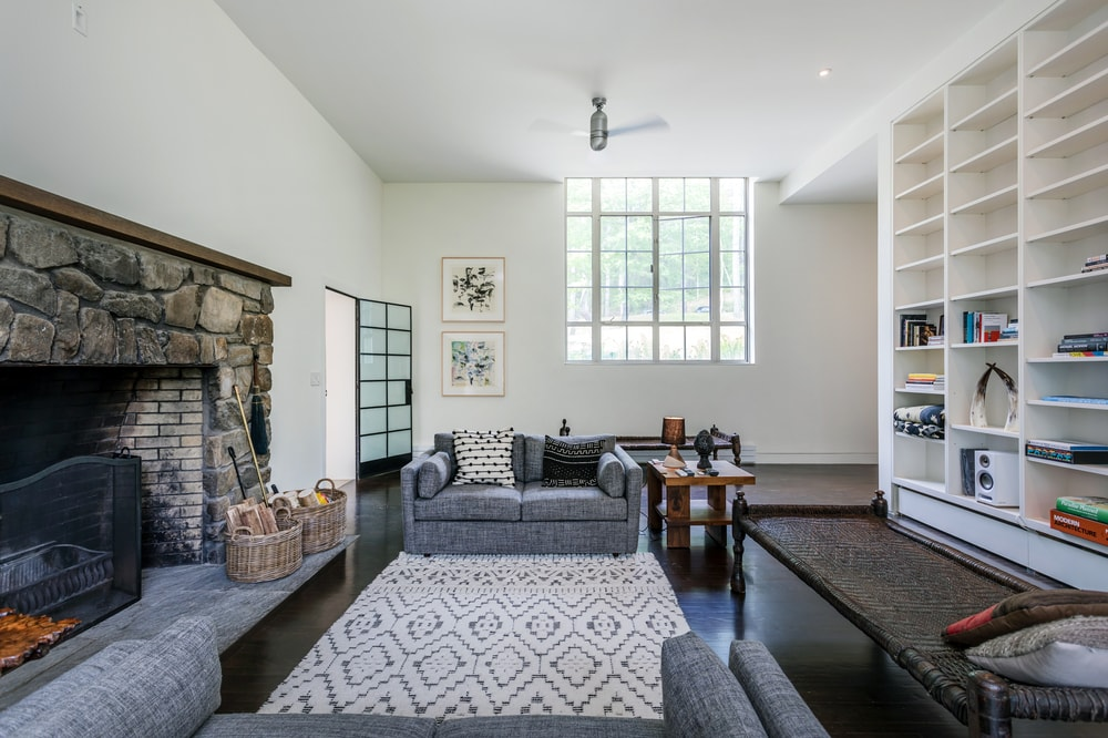The two gray armchairs have a gray patterned area rug in the middle that contrasts the dark hardwood flooring. Image courtesy of Toptenrealestatedeals.com.