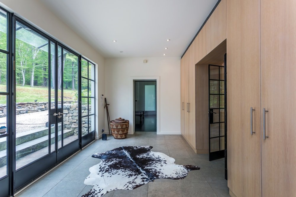 This other view of the foyer showcases an animal fur area rug in the middle and a couple of rustic decorations at the corner. Image courtesy of Toptenrealestatedeals.com.