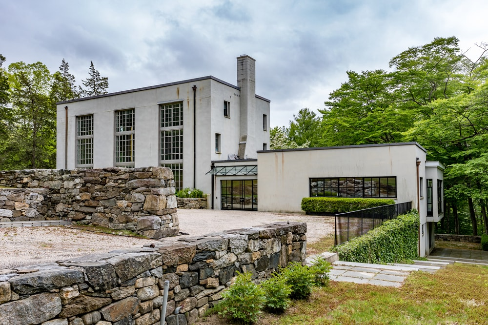 This is a view of the front of the house showcasing the landscaping of stone mosaic walls that are adorned with shrubs. Image courtesy of Toptenrealestatedeals.com.