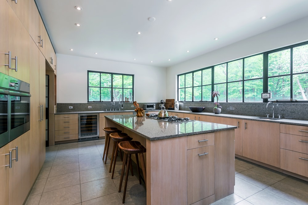 The kitchen has a large kitchen island in the middle of the tiled floor. Image courtesy of Toptenrealestatedeals.com.