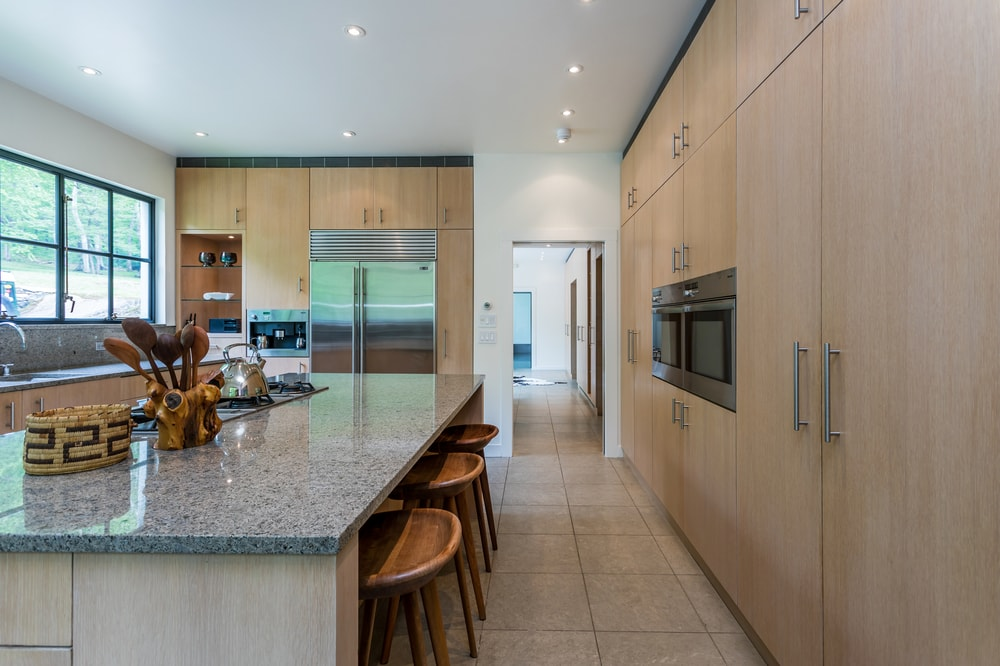 On one side of the kitchen island is a large wooden structure that houses wooden cabinets and the embedded appliances. Image courtesy of Toptenrealestatedeals.com.
