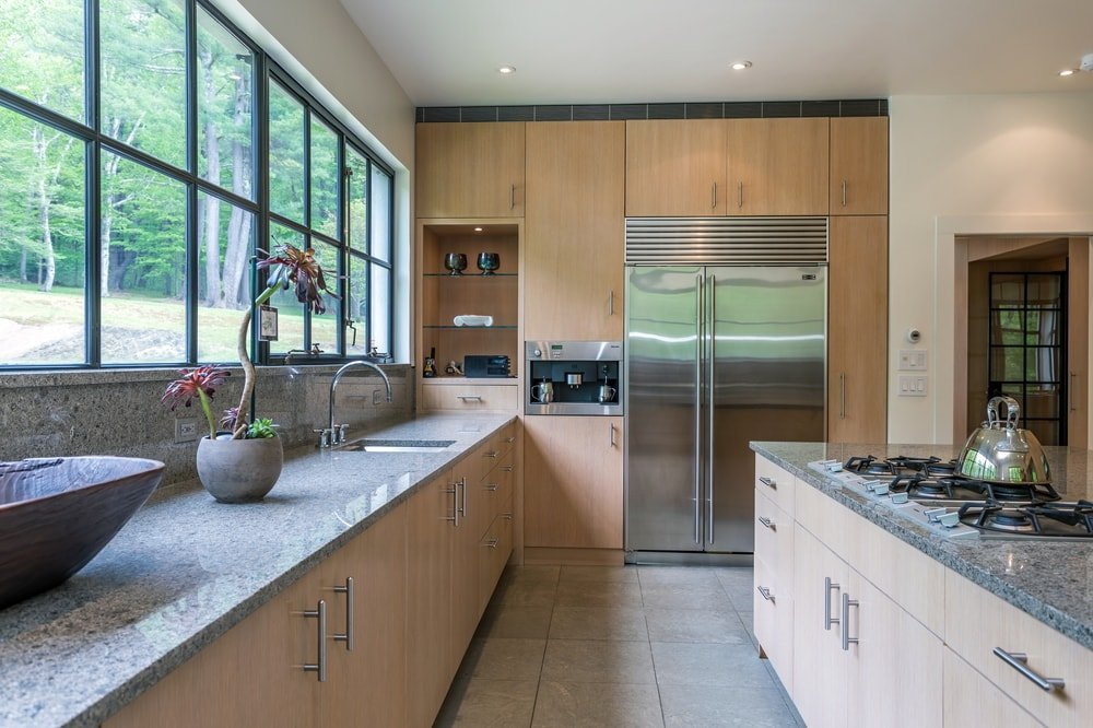 This angle of the kitchen features the large stainless steel fridge on the far side embedded into the wooden wall. Image courtesy of Toptenrealestatedeals.com.