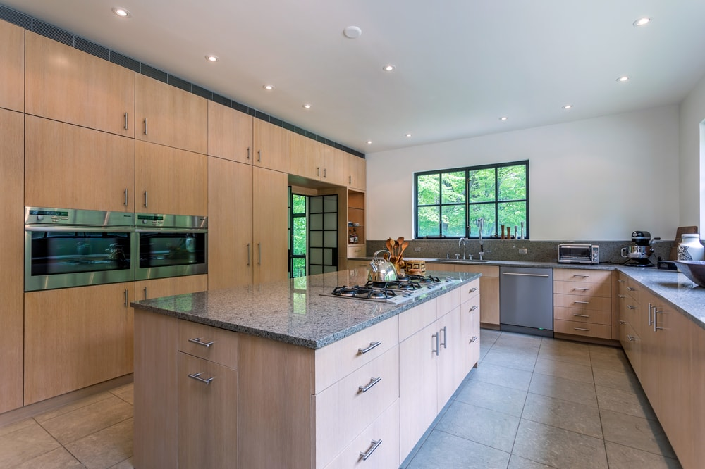 The cooking area of the kitchen is housed by the kitchen island that is topped with a white ceiling. Image courtesy of Toptenrealestatedeals.com.