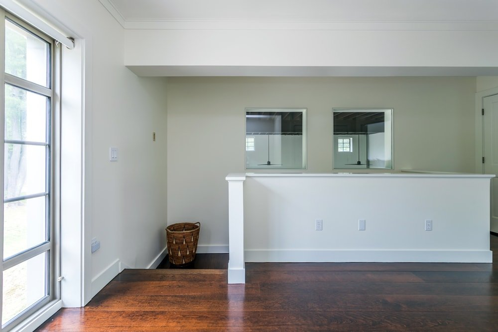 This is the second-floor landing of the house that has a dark hardwood flooring that contrasts the white walls and ceiling. Image courtesy of Toptenrealestatedeals.com.