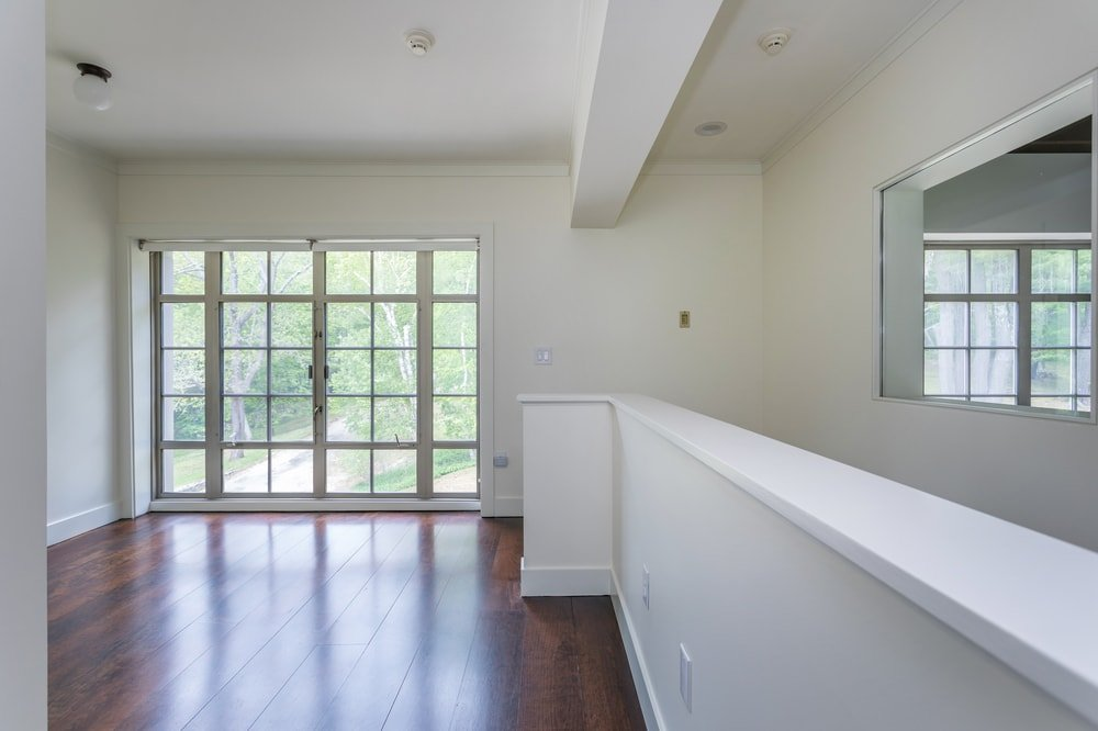 This angle of the second-floor landing shows the set of glass doors on the far end leading to the outdoor areas of the property. Image courtesy of Toptenrealestatedeals.com.