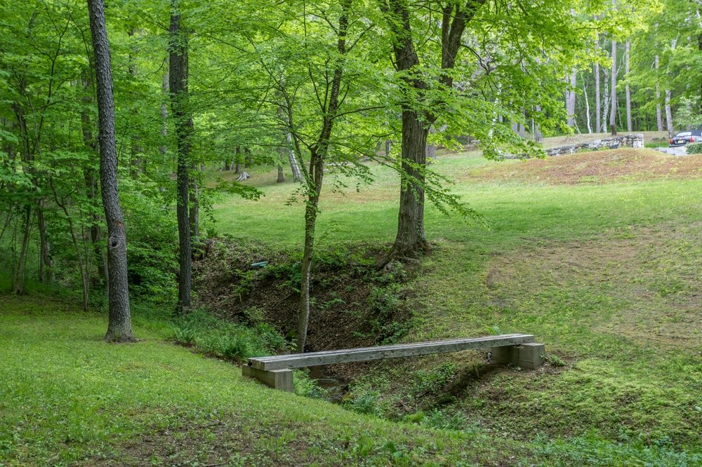 This is a quiet corner of the property with a small bridge crossing the shallow stream. Image courtesy of Toptenrealestatedeals.com.
