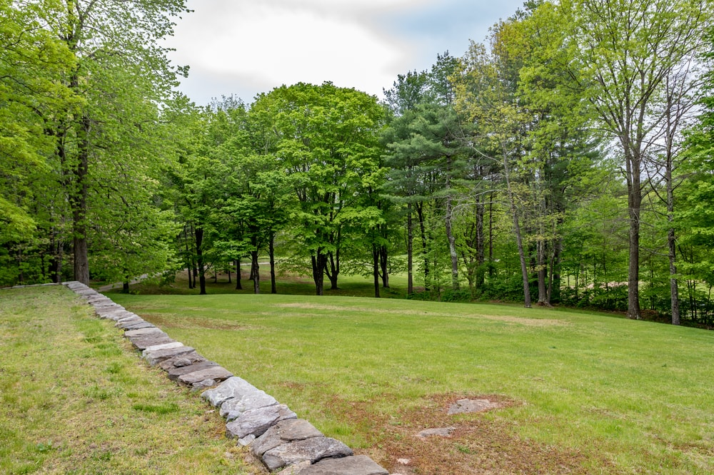 This part of the surrounding landscape showcases the tall mature trees of the property as well as the grass lawn. Image courtesy of Toptenrealestatedeals.com.
