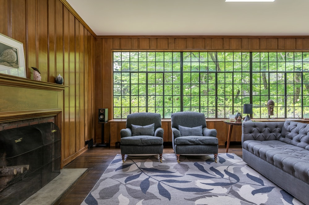 This is a close look at the couple of gray cushioned armchairs beside the gray sofa. This has a background of a large window showing the tall trees outside. Image courtesy of Toptenrealestatedeals.com.