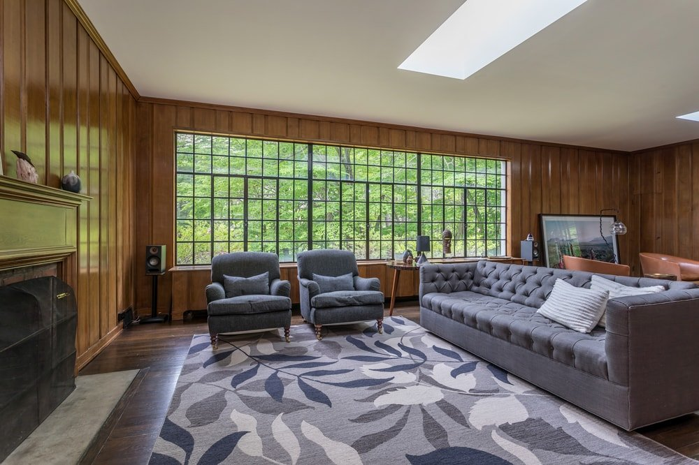 This angle of the living room showcases the large gray patterned area rug on the hardwood flooring. This matches well with the gray sofa set. Image courtesy of Toptenrealestatedeals.com.