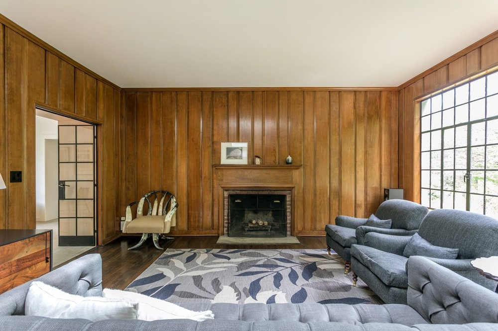 This view of the living room shows the fireplace on the far wall that has a dark wooden tone to match the floor and contrast the white ceiling. Image courtesy of Toptenrealestatedeals.com.