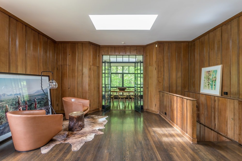 This part of the living room leads to the dining room and is fitted with a small sitting area on the side with a large painting. This is then topped with a skylight for natural lighting. Image courtesy of Toptenrealestatedeals.com.