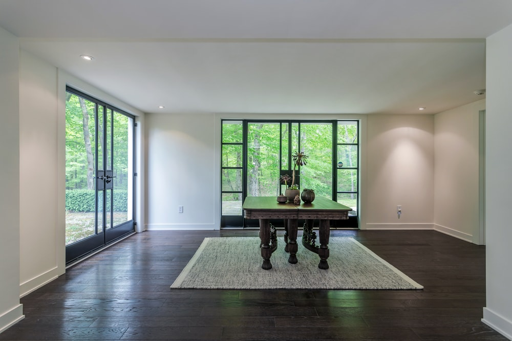 The lower level foyer has a dark wooden table in the middle that matches with the hardwood flooring that contrasts the bright walls and ceiling. Image courtesy of Toptenrealestatedeals.com.