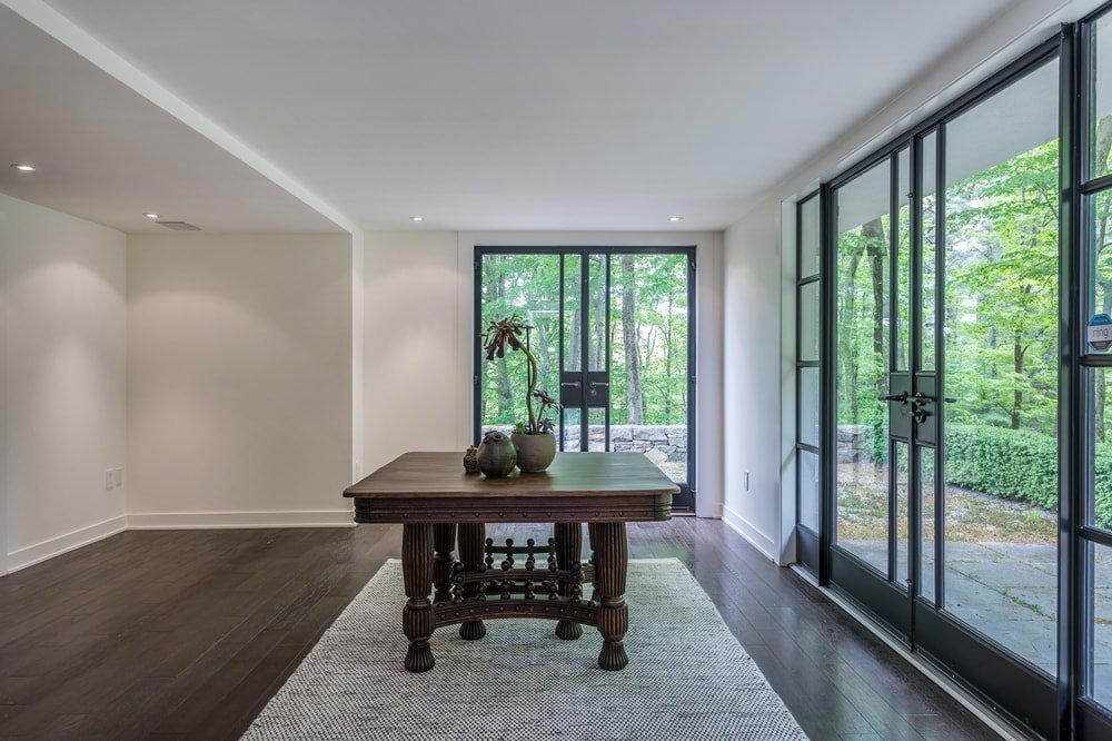 This other view of the lower level foyer showcases the glass doors that provide natural lighting as well as background showing the landscape outside. Image courtesy of Toptenrealestatedeals.com.