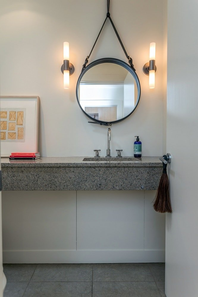 A closer look at the powder room showcases a floating vanity topped with a round mirror flanked by wall-mounted lamps. Image courtesy of Toptenrealestatedeals.com.