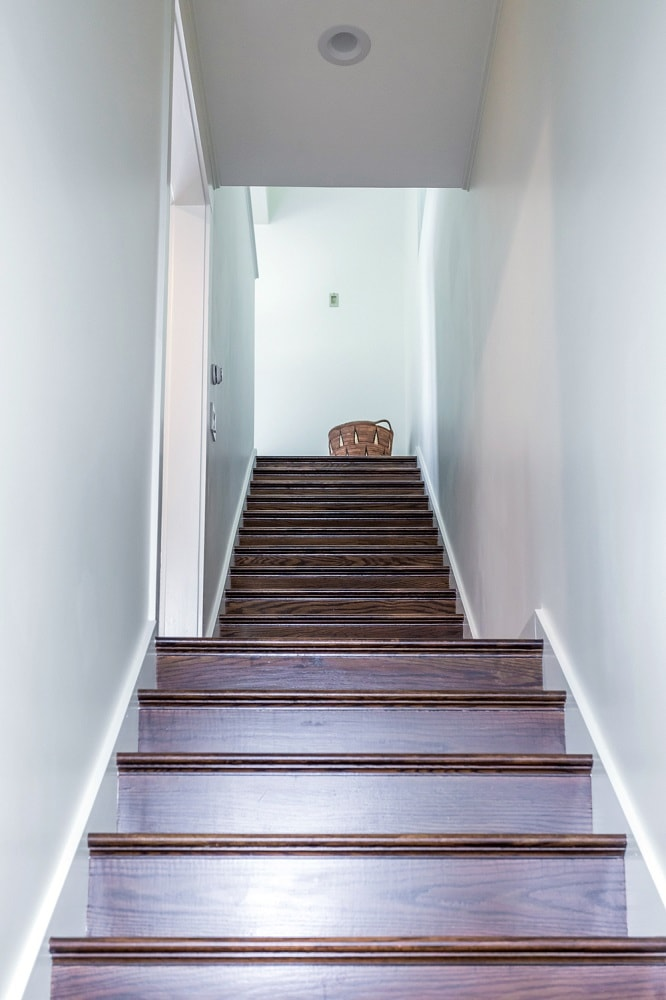 The staircases has dark wooden steps that contrast the light tone of the walls on either side. Image courtesy of Toptenrealestatedeals.com.