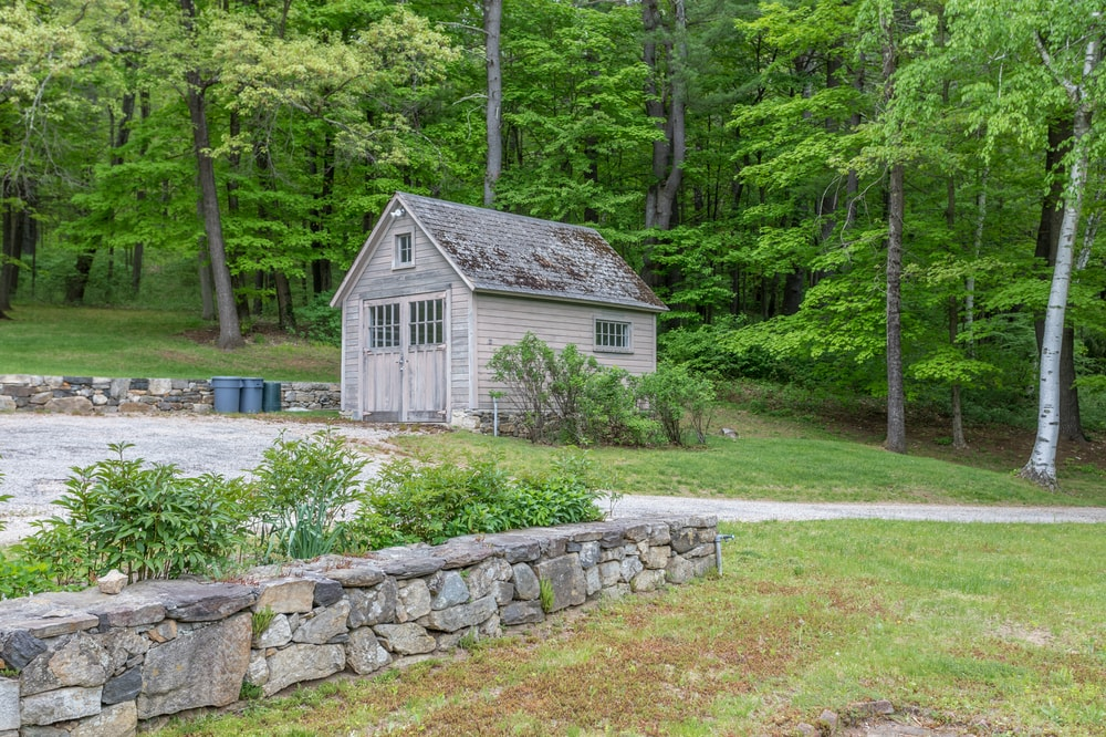 This is the storage cabin of the property surrounded by a landscaping of tall trees and grass lawns. Image courtesy of Toptenrealestatedeals.com.