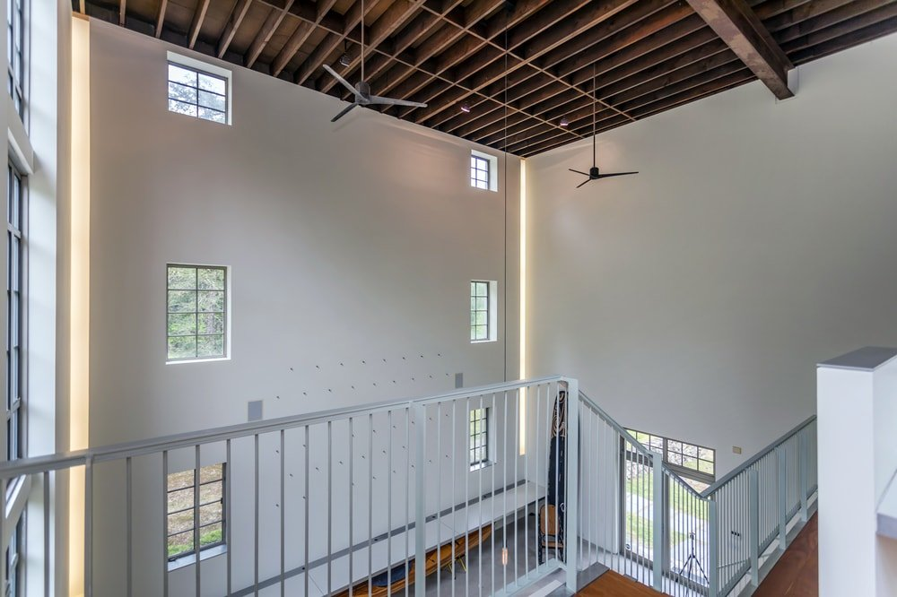 This is a view of the indoor balcony of the studio with white railings to match the tall walls. Image courtesy of Toptenrealestatedeals.com.