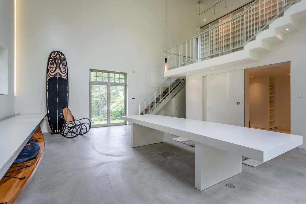 This large white table is topped with a pendant light that hangs from the tall ceiling. You can also see here the glass doors of the entrance. Image courtesy of Toptenrealestatedeals.com.