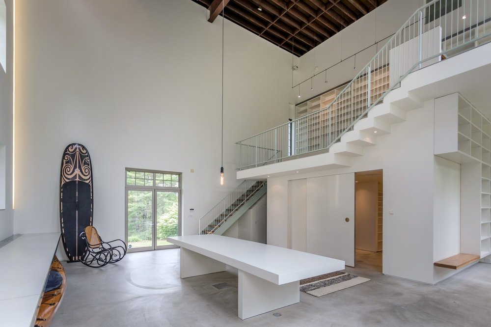 The studio has tall white walls that matches with the white stairs and the large white table in the middle of the concrete floor. Image courtesy of Toptenrealestatedeals.com.