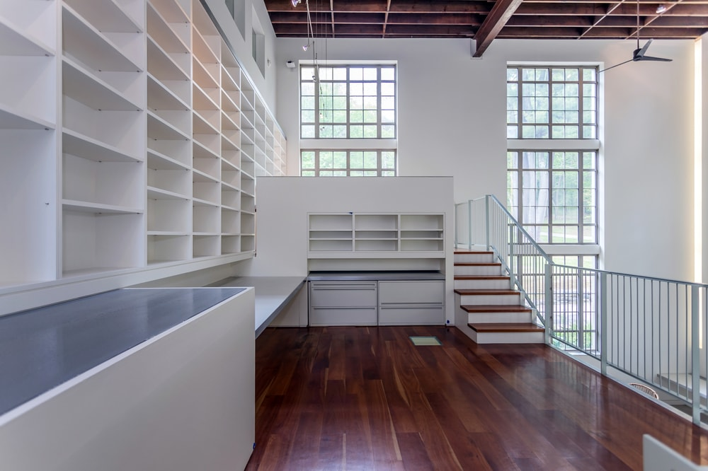 This view of the second level showcases the dark hardwood flooring that contrasts the walls and built-in shelves. Image courtesy of Toptenrealestatedeals.com.