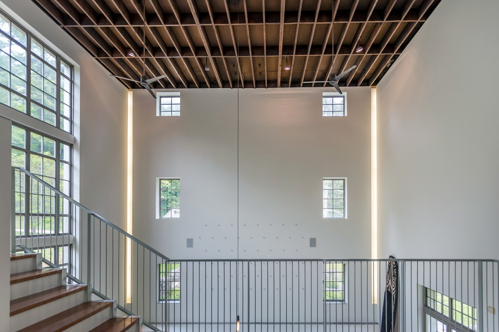 The indoor balcony of the studio looks over the large open area with a tall ceiling made of wood. Image courtesy of Toptenrealestatedeals.com.