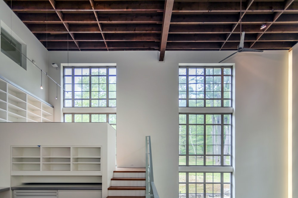 This is a look at the second-floor landing of the studio that is brightened by the couple of tall windows. Image courtesy of Toptenrealestatedeals.com.