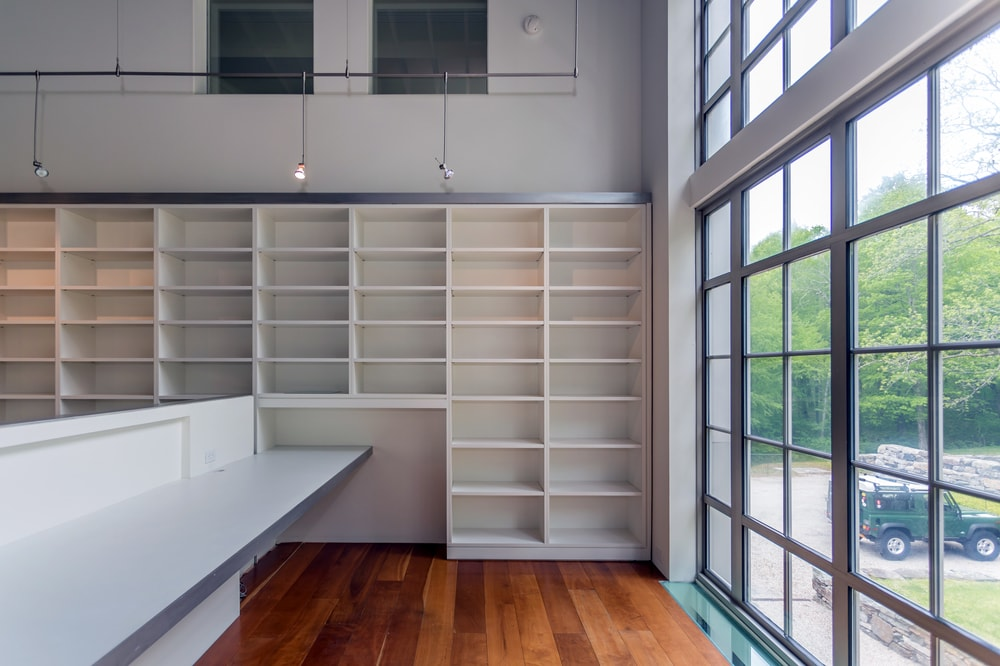 This side of the studio has built-in wooden shelves. Next to it is a large wall of glass that bring in natural lighting. Image courtesy of Toptenrealestatedeals.com.