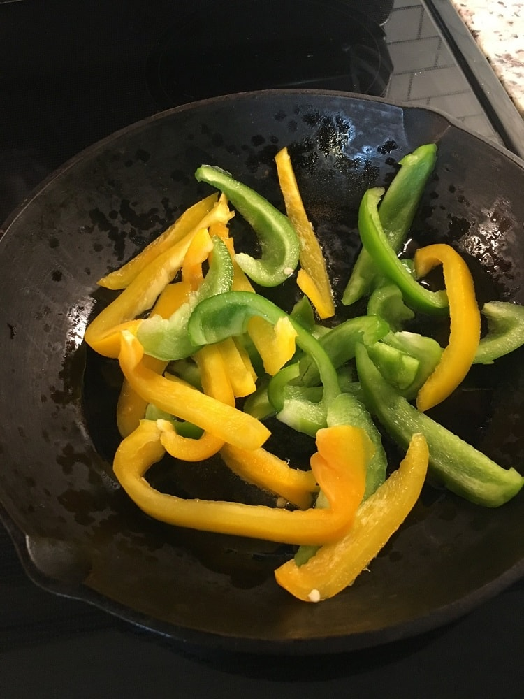 The peppers and onion are cooked on the pan.
