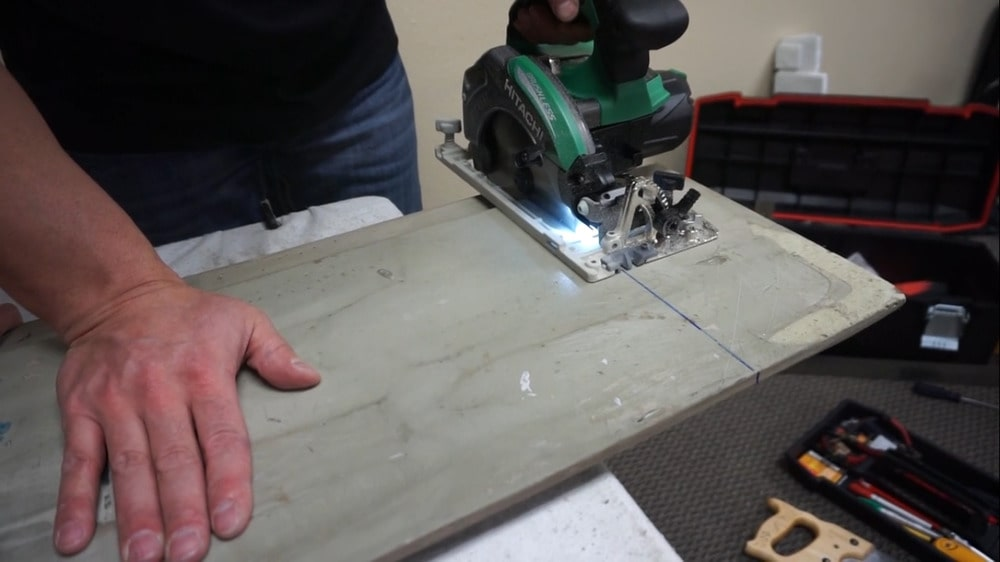 Cutting out pieces of the panel using a hole saw.