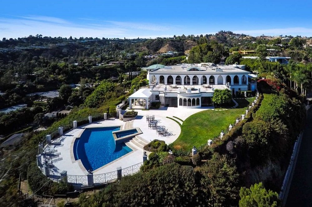 This is an aerial view of the mansion showcasing its bright exteriors filled with open arches that stand out against the surrounding landscape filled with trees and shrubs. Image courtesy of Toptenrealestatedeals.com.