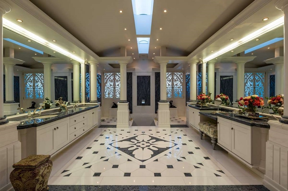 This is a spacious bathroom with patterns on its flooring tiles. This is flanked by the two vanities built into the two walls leading to the shower area at the far end with pillars. Image courtesy of Toptenrealestatedeals.com.