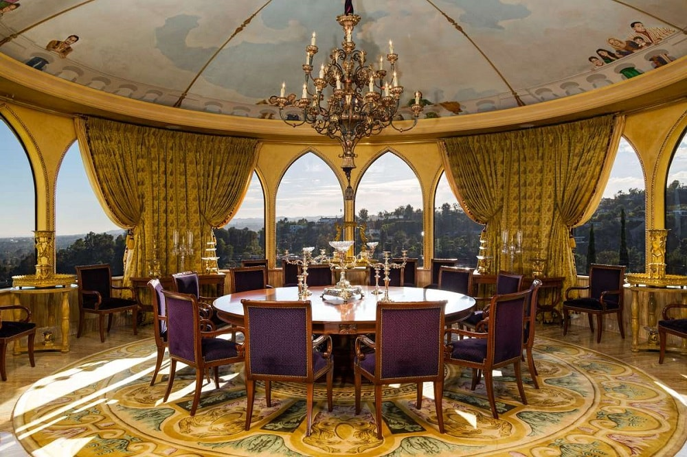 The formal dining area has a large chandelier hanging from a dome ceiling over a large round table. These are then complemented by the surrounding open arches. Image courtesy of Toptenrealestatedeals.com.