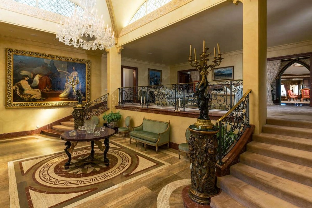 Upon entry of the house, you are welcomed by this foyer that has a large crystal chandelier hanging over a round dark wooden table on a patterned marble floor. Image courtesy of Toptenrealestatedeals.com.