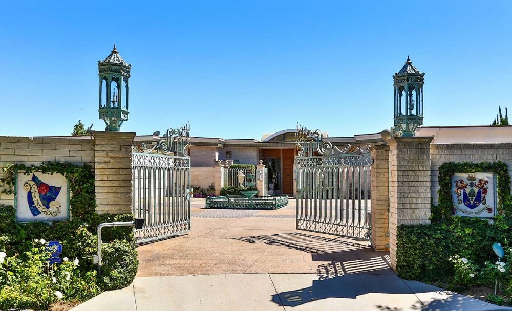 This is the main gate of the mansion with large wrought-iron gates supported by tall stone columns with decorative outdoor lighting on top. Image courtesy of Toptenrealestatedeals.com.