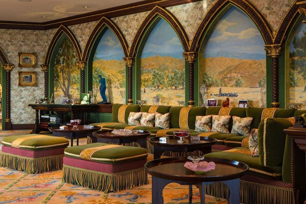 The living room is complemented by the colorful patterns of the carpeted flooring and the walls filled with arches and murals. Image courtesy of Toptenrealestatedeals.com.