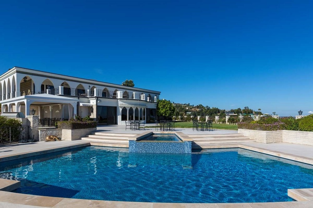 This is a look at the house from the vantage of the pool. You can see here that the pool has concrete steps that lead from the terrace just outside the arches of the house. Image courtesy of Toptenrealestatedeals.com.