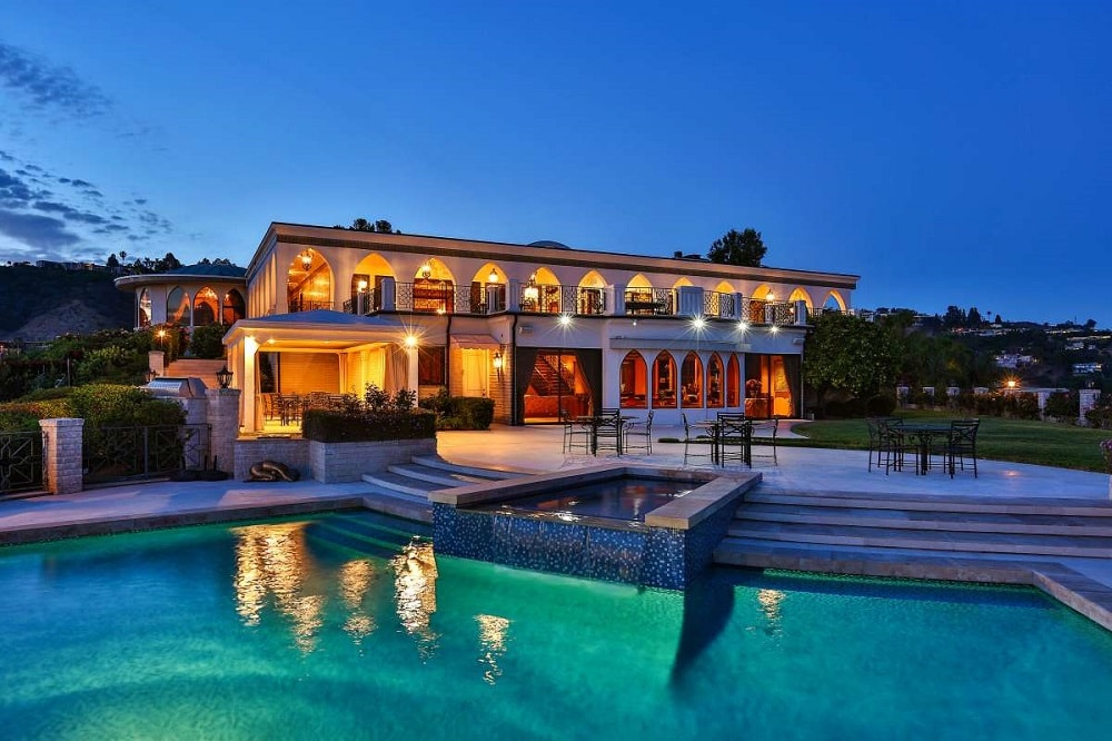 This is a nighttime view of the house from the vantage of the pool. Here you can see the multiple rows of arches of the house light up with a warm yellow light. Image courtesy of Toptenrealestatedeals.com.