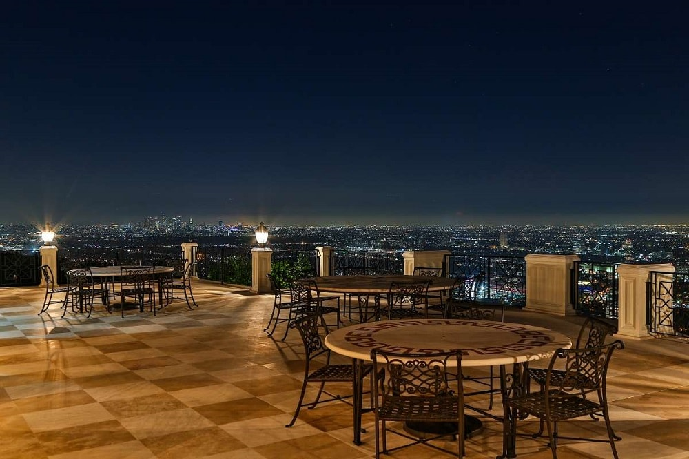 This is a nighttime view of the outdoor dining area on the terrace. Here, you can see more of the checkered flooring tiles and the outdoor lighting that gives the area a warm glow. Image courtesy of Toptenrealestatedeals.com.