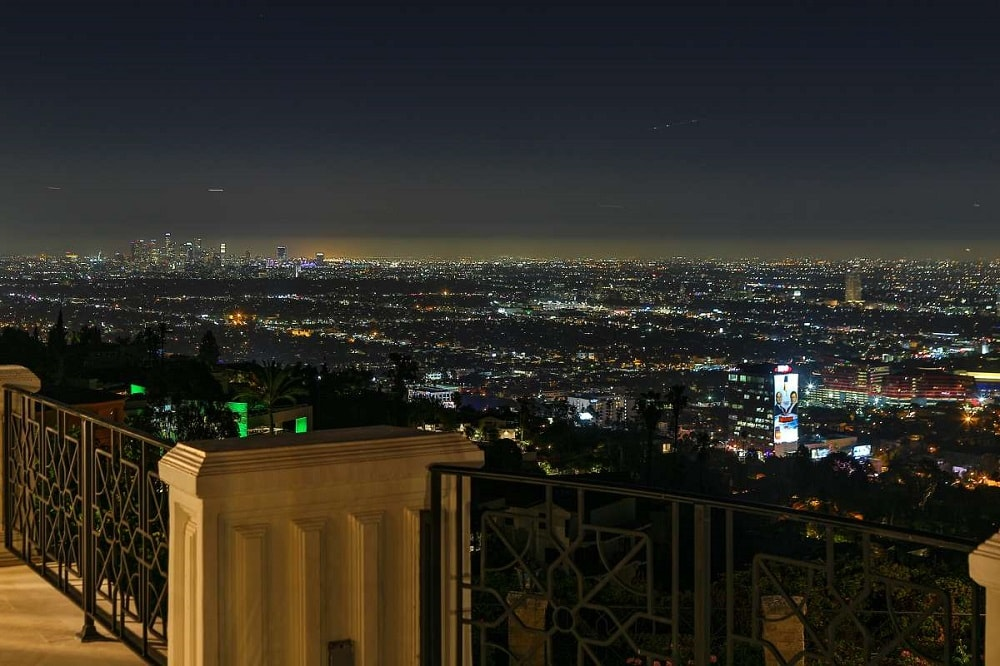 This is a closer look at the railings overlooking the sweeping city views. Here you can see the details of the wrought-iron railings supported by waist-high concrete posts. Image courtesy of Toptenrealestatedeals.com.