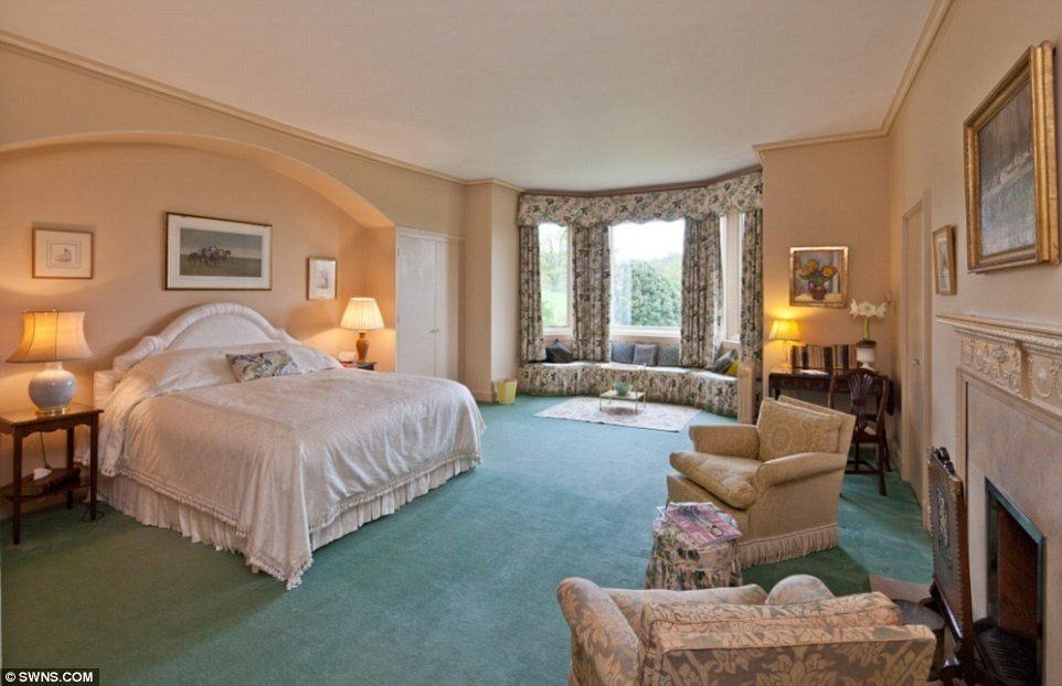 This bedroom has beige walls, and a beige ceiling that matches the bed. and the armchairs across the room. These are then complemented by the blue-green carpet. Image courtesy of Toptenrealestatedeals.com.