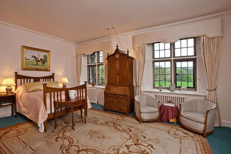 This bedroom has a wooden sleigh bed that matches perfectly with the wooden dresser on the side that is flanked by large windows. Image courtesy of Toptenrealestatedeals.com.